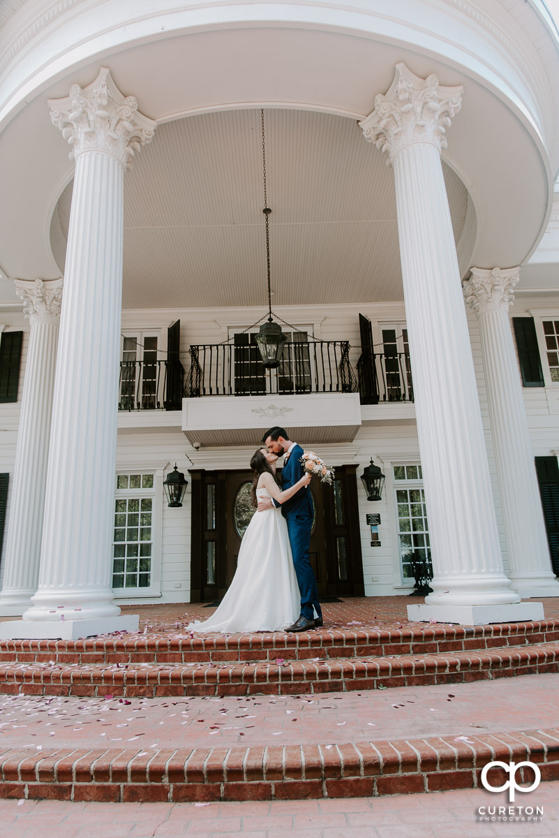 Bride and groom kissing on the porch of the Ryan Nicholas Inn.