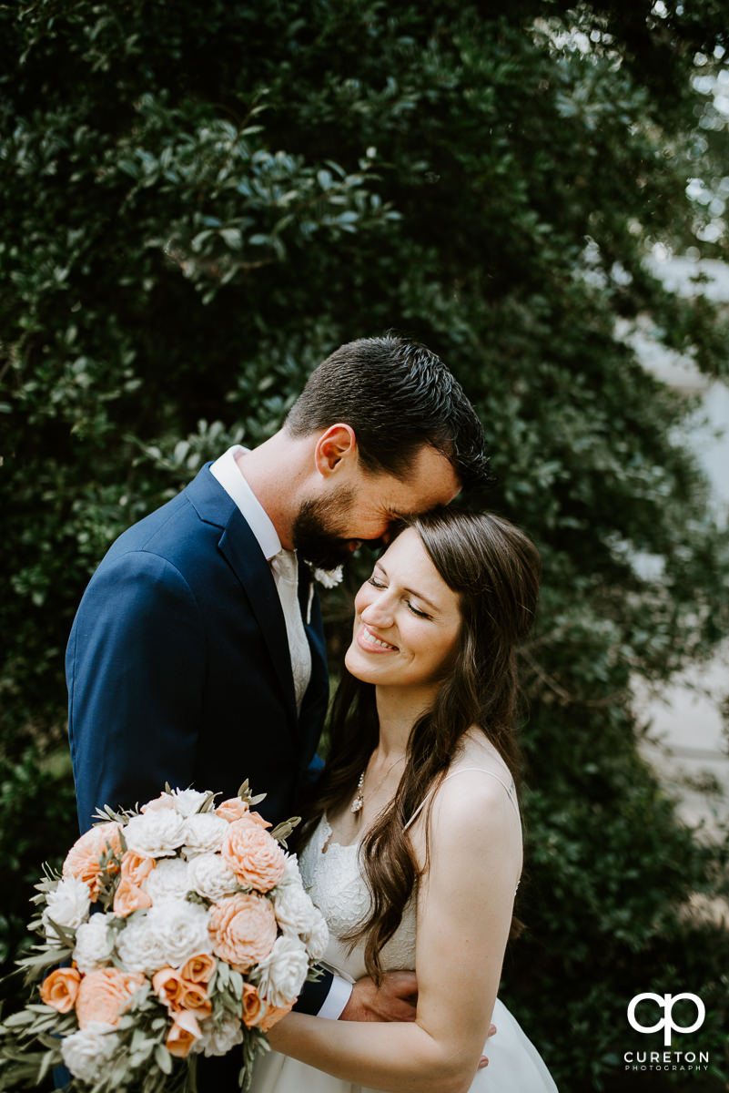 Bride and groom snuggling in front of some greenery at the Ryan Nicholas Inn.