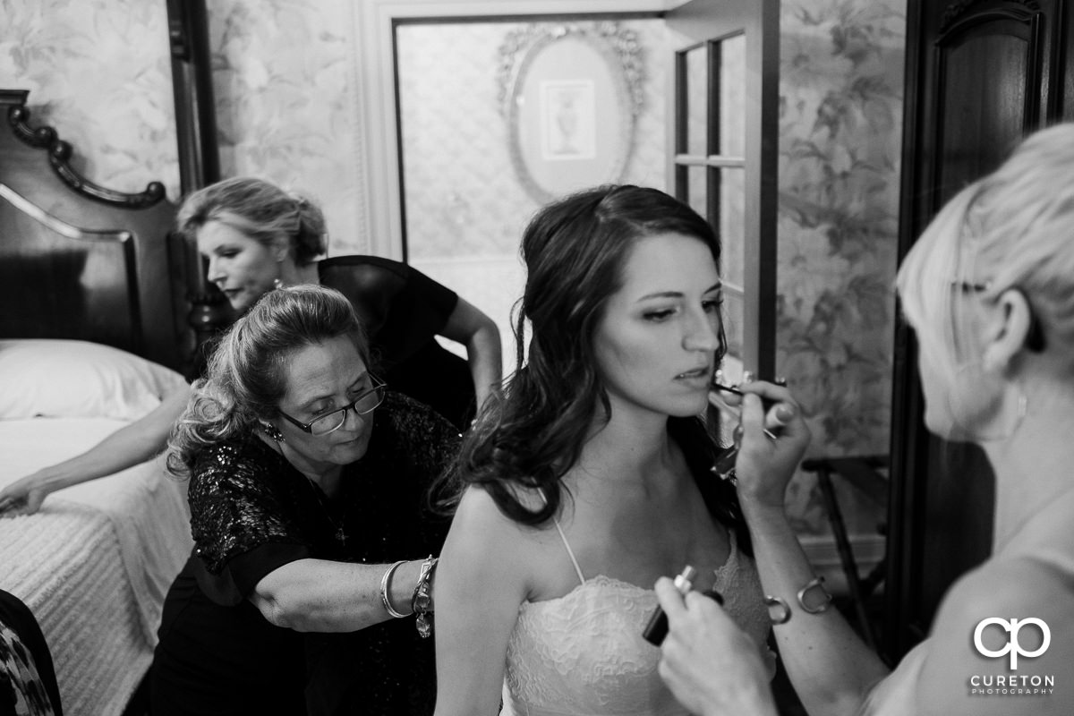 Bride getting into her dress before the ceremony.