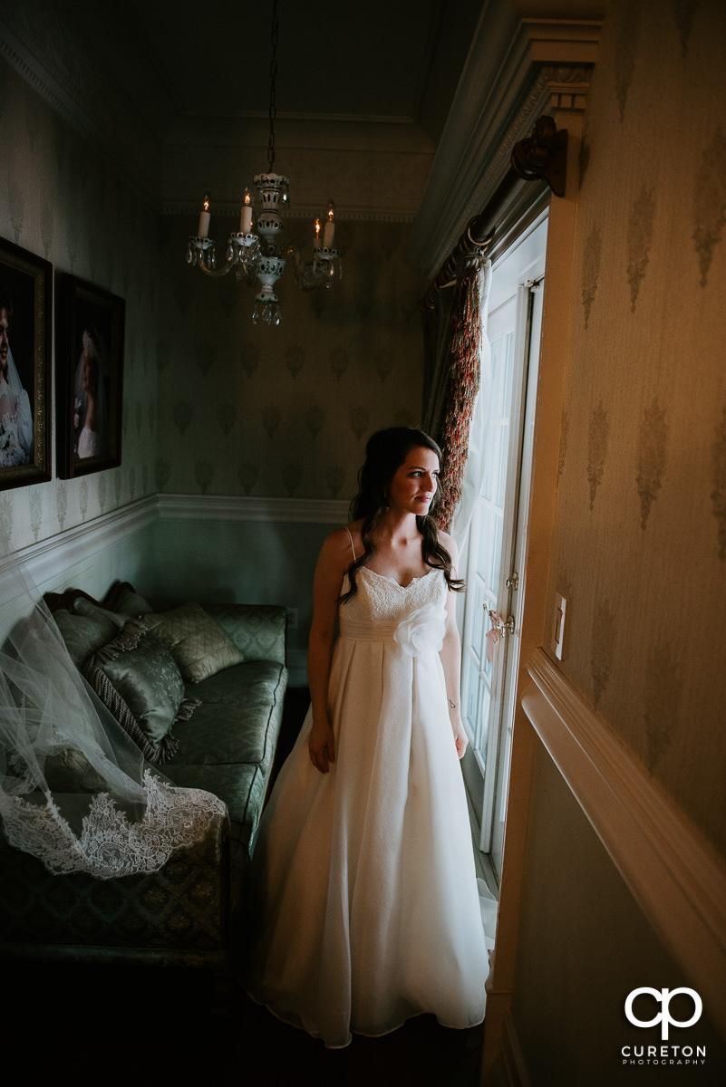 Bride standing in window light in the bridal suite in the Ryan Nicholas Inn before her wedding.