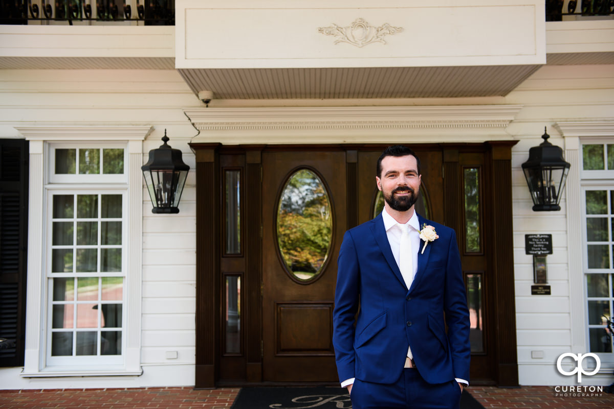 Groom on the porch of the Ryan Nicholas Inn awaiting the first look with his bride.