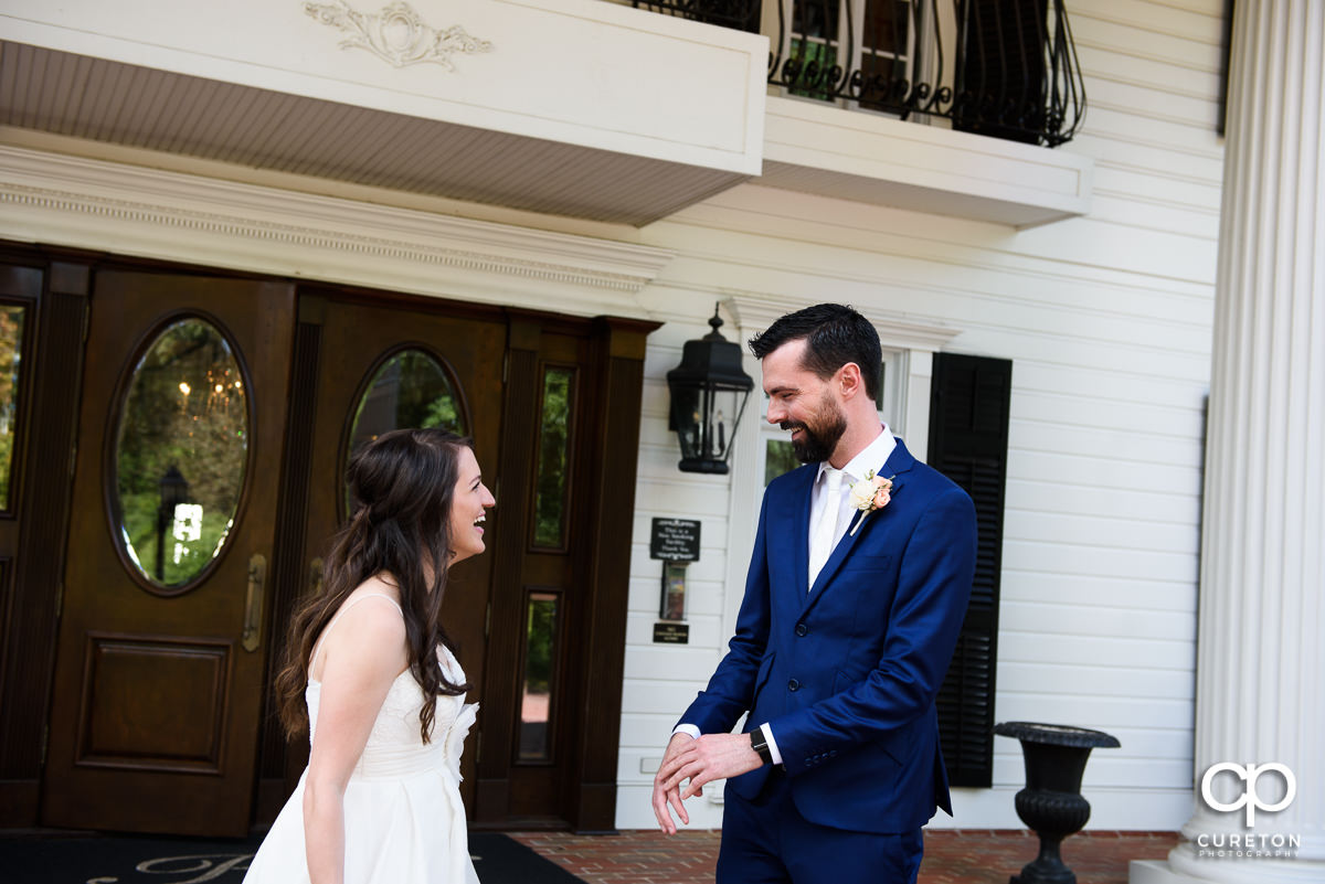 Bride and groom sharing a first look on the porch of the Ryan Nicholas Inn before their wedding.