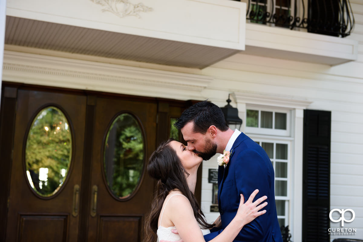 Bride and groom kissing at the first look.
