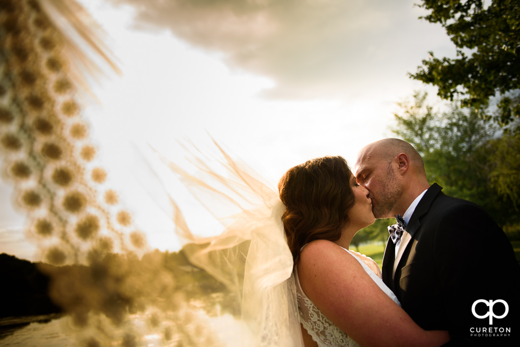 Bride kissing her groom with her veil blowing in the wind at the South Wind Ranch, a wedding venue in Travelers Rest, SC.
