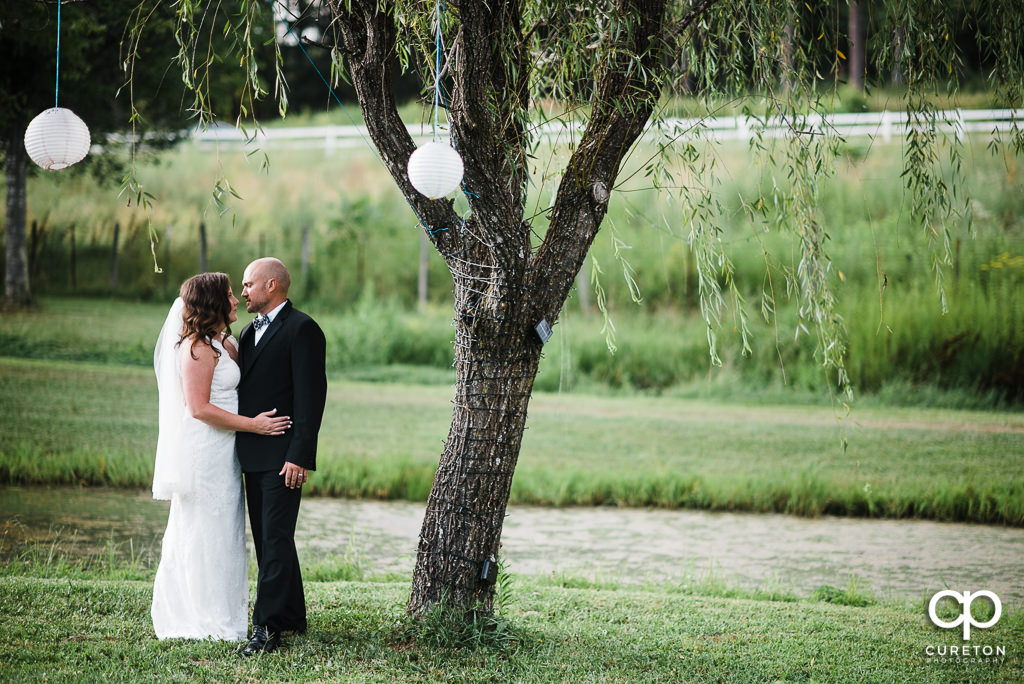 Bride and Groom standing by a tree at South Wind Ranch.