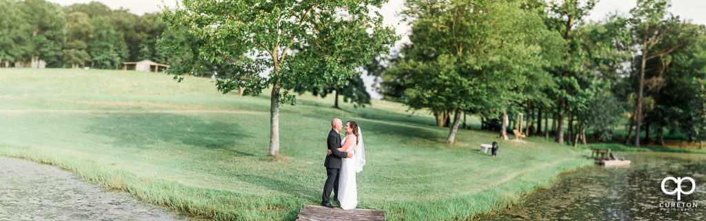 Pano of a bride and groom by the lake at South Wind Ranch.