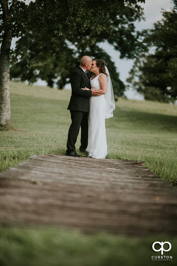 Bride and groom kissing on a dock at South Wind Ranch.