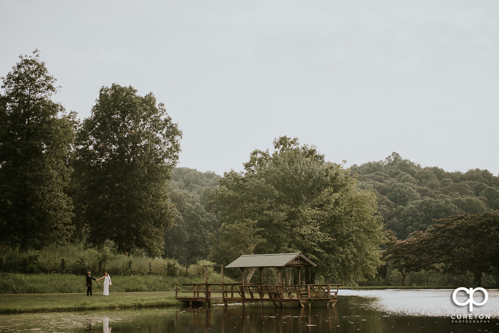 Bride and Groom walking by the lake at South Wind Ranch in Travelers Rest SC.