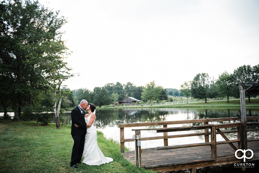 Bride and groom kissing near the dock on the lake at South Wind Ranch, a wedding venue in Travelers Rest SC.