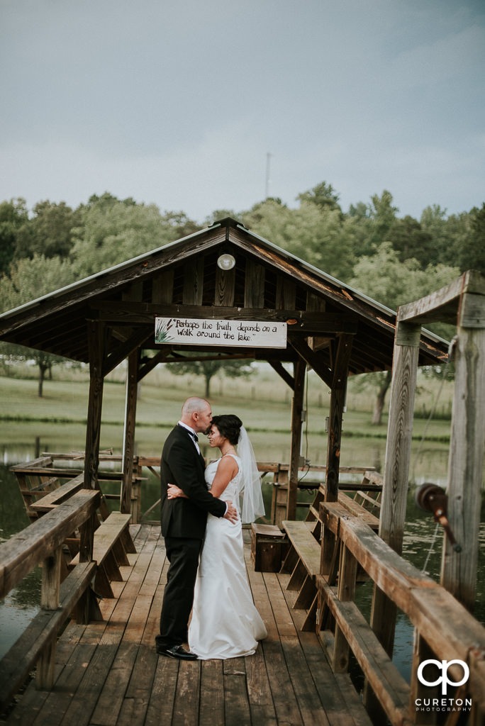 Groom kissing his bride on the forehead at the South Wind Ranch, a wedding venue in Travelers Rest, SC.