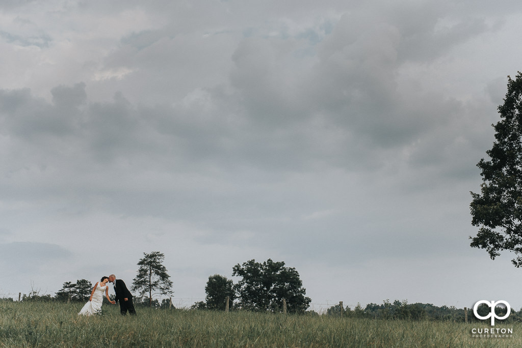 Bride and groom kissing in a field at South Wind Ranch.