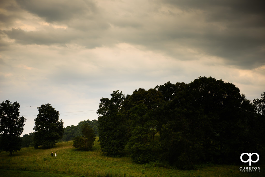 Bride and Groom walking up a hill after their wedding at South Wind Ranch in Travelers Rest SC.