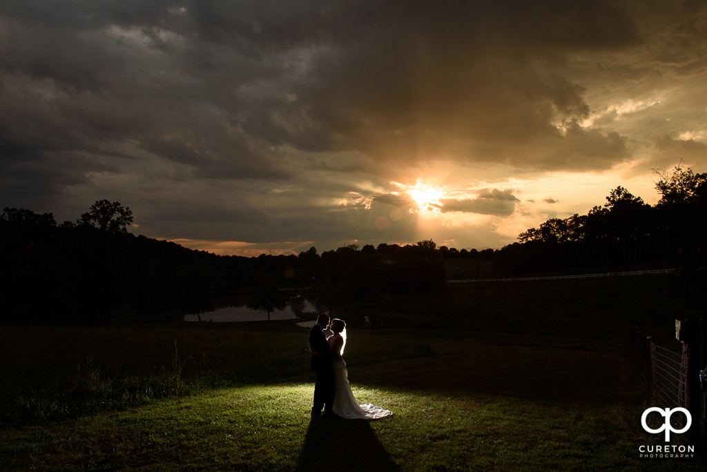 Bride and groom silhoueet at sunset after their wedding at South Wind Ranch in Travelers Rest SC.