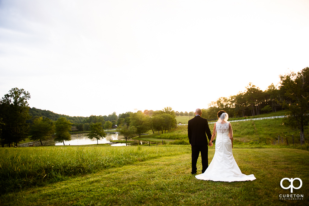 Bride and groom looking at the lake at the South Wind ranch.