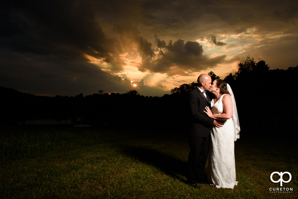 Bride and groom kissing at sunset.
