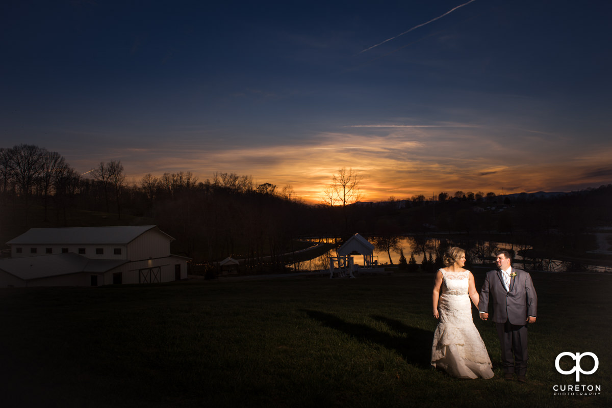 Bride and groom standing in a field at sunset during their South Wind Ranch wedding in Travelers Rest,SC.