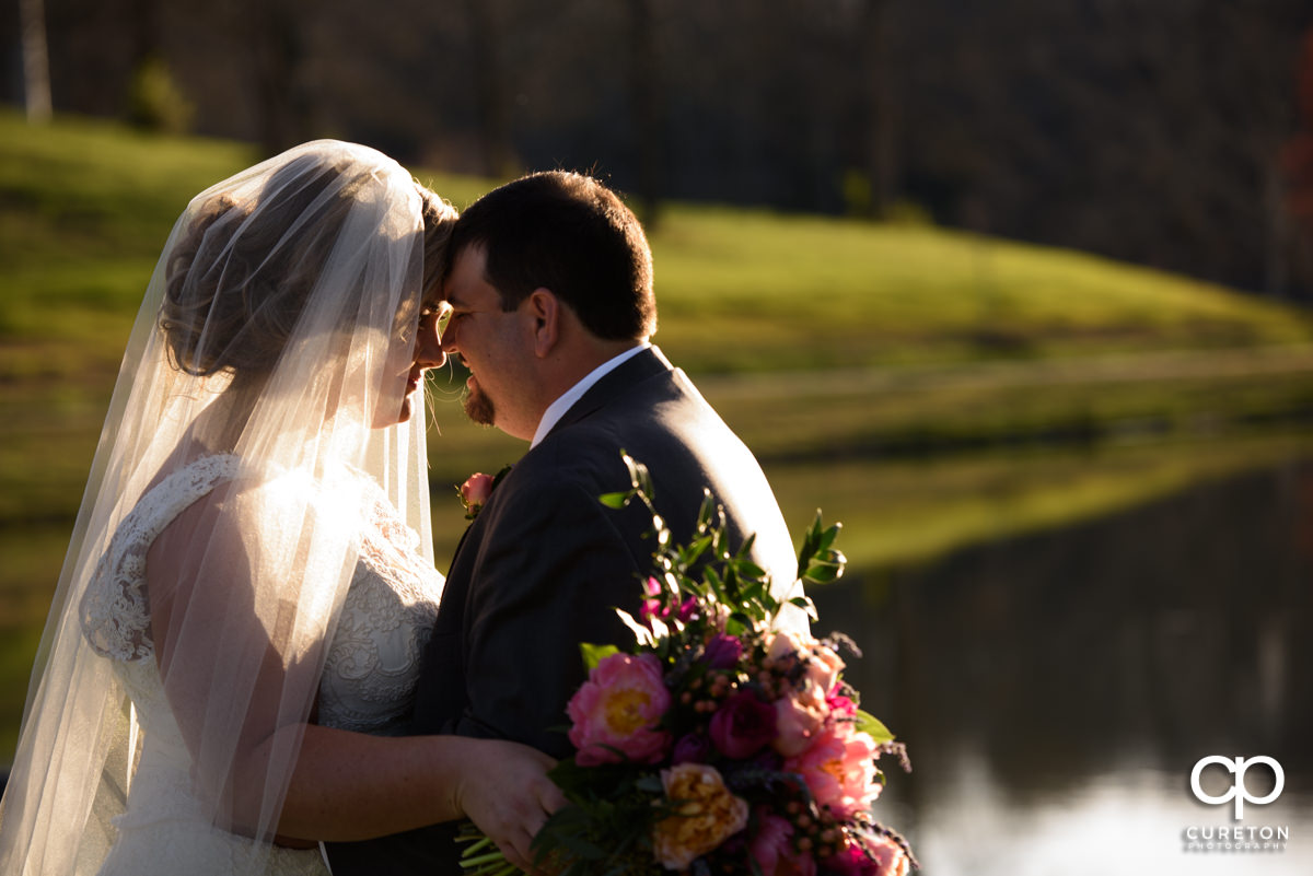 Bride and groom snuggling by the lake during their South Wind Ranch wedding in Travelers Rest,SC.