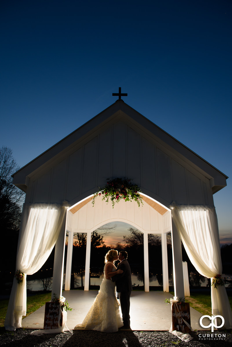 Bride and groom kissing underneath the outdoor chapel at sunset during their South Wind Ranch wedding in Travelers Rest,SC.