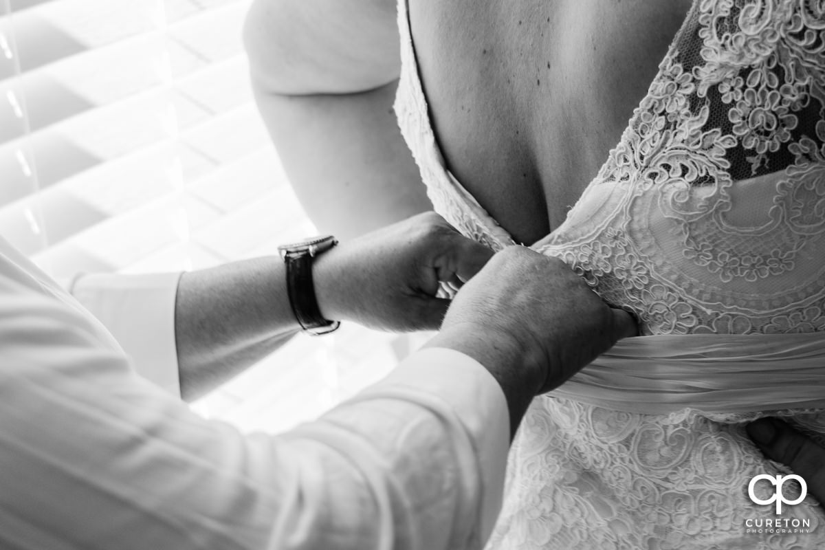 Bride getting help into her dress.