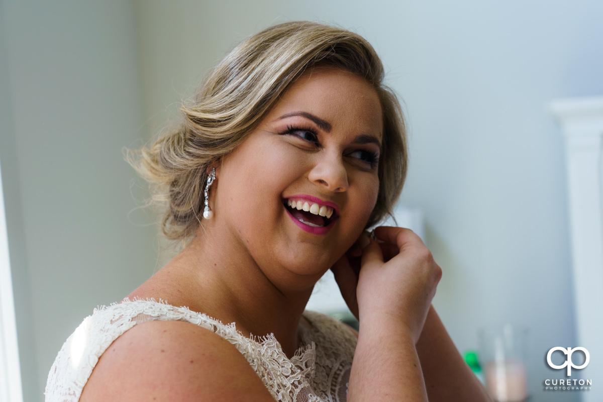 Bride putting on her earrings.