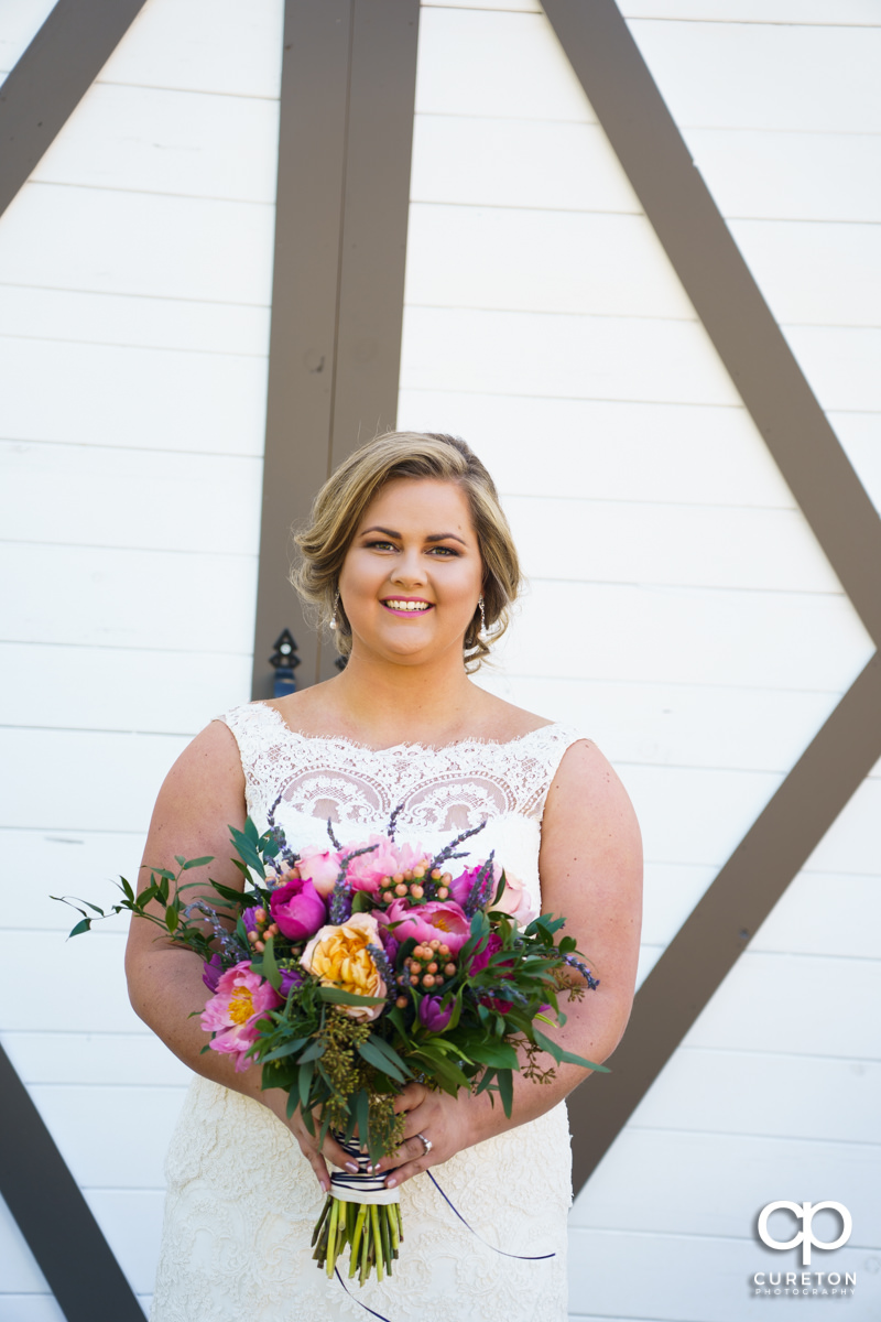 Bride holding her flowers in front of the barn doors at South Wind Ranch.