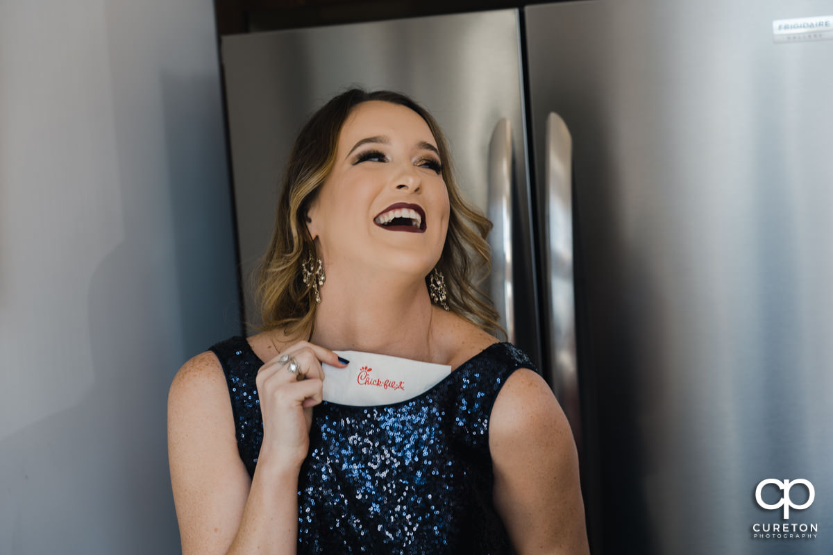 Bridesmaid pulling a chick fil a sandwich out of her dress.