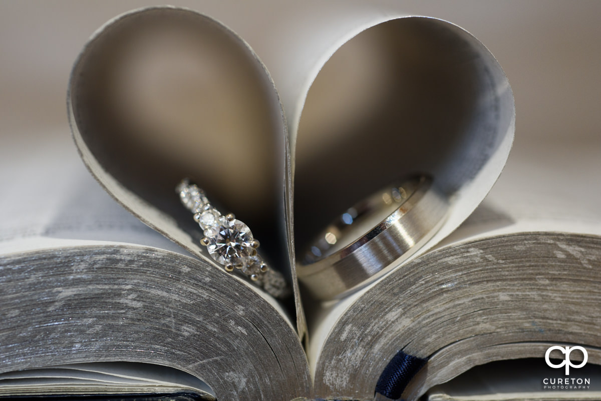 Wedding Rings in a Bible making a heart out of the pages.