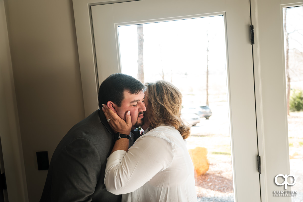 Groom's mom kissing her son on the cheek as she helps him get ready.