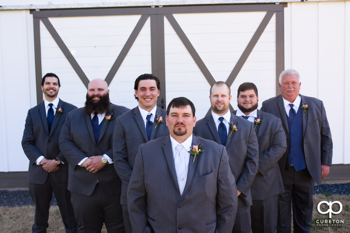 Groom and groomsmen standing in front of a barn door at South Wind Ranch.
