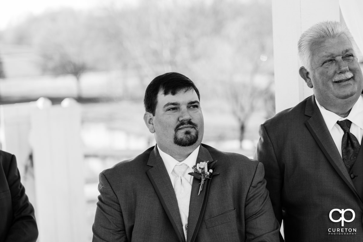 Groom seeing his bride walk down the aisle for the first time.
