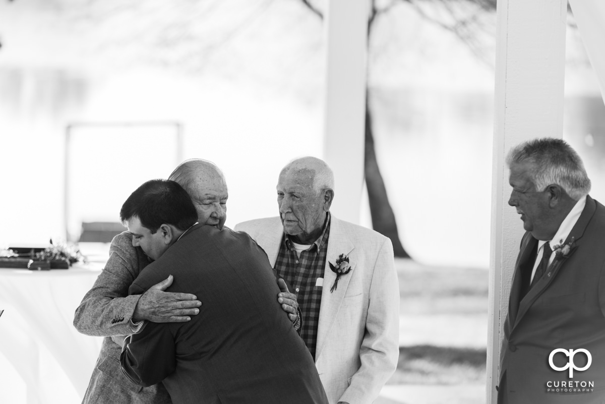 Groom hugging his grandpa at the wedding ceremony.