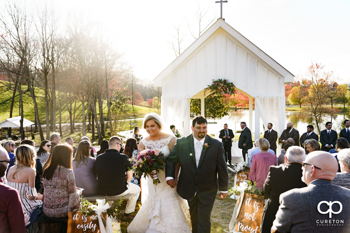 Bride and groom walking back up the aisle during their South Wind Ranch wedding in Travelers Rest,SC.