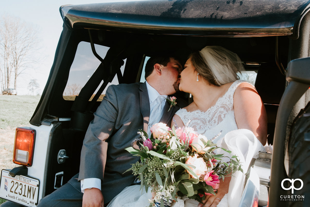 Bride and groom kissing in the back of a jeep.