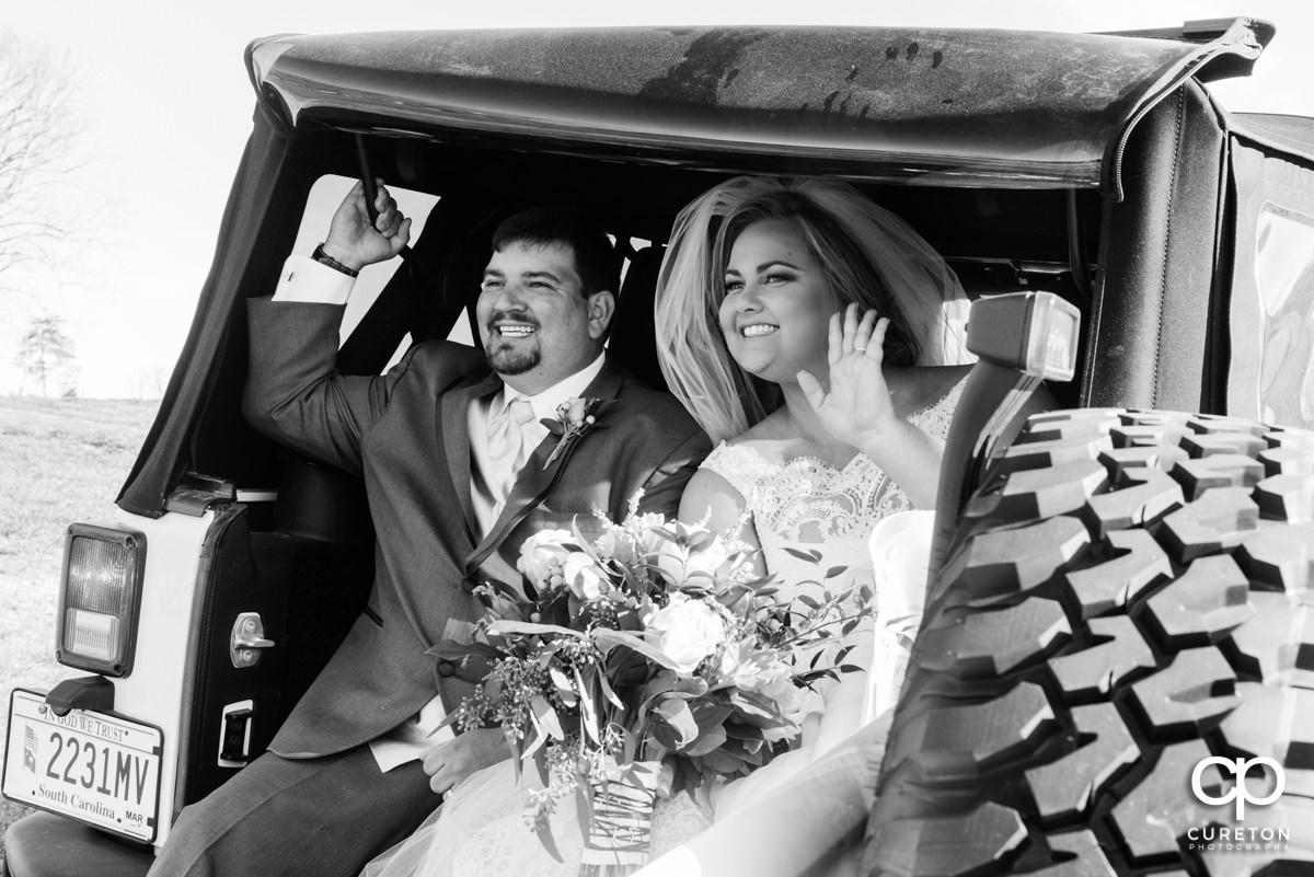 Bride and groom leaving the ceremony in the back of a Jeep.