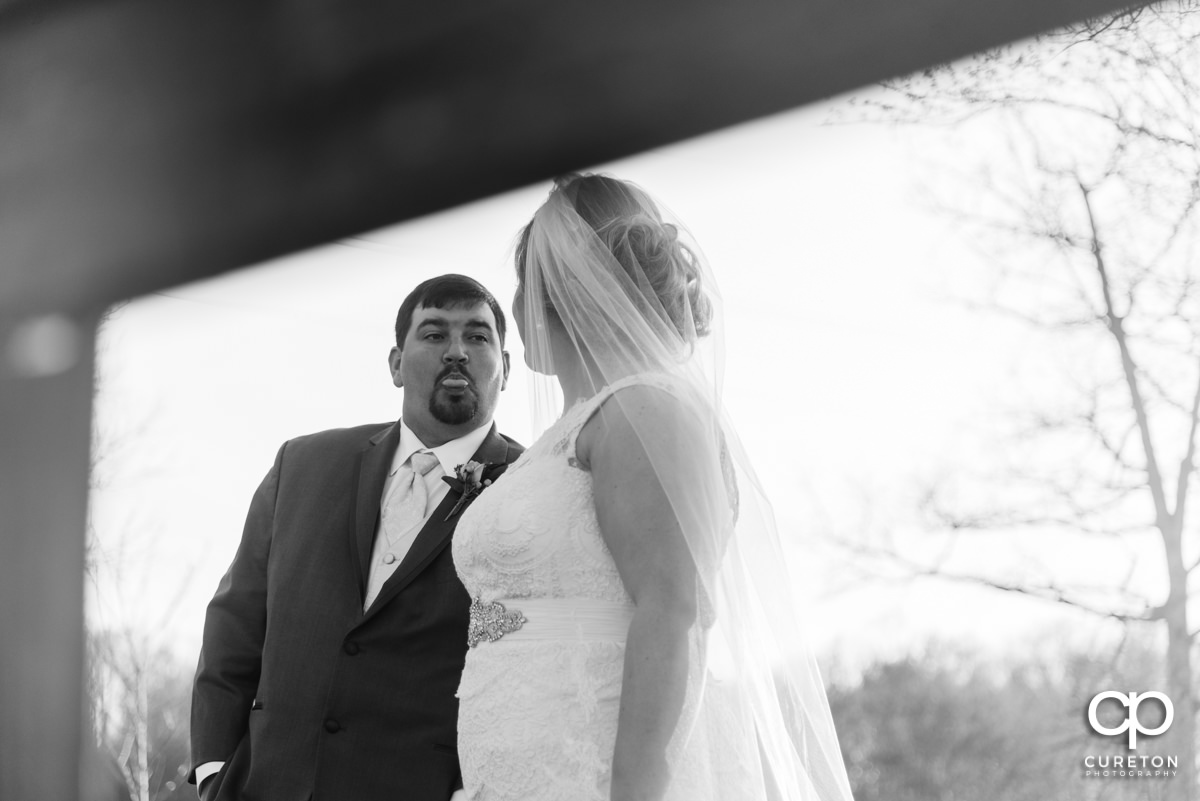 Groom sticking his tongue out at the bride.