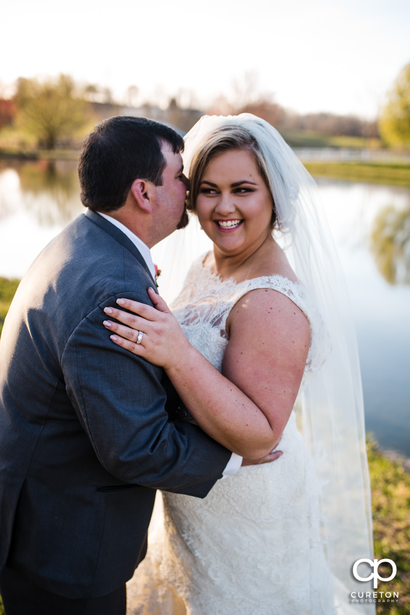 Groom whispering in the bride's ear during their South Wind Ranch wedding in Travelers Rest,SC.