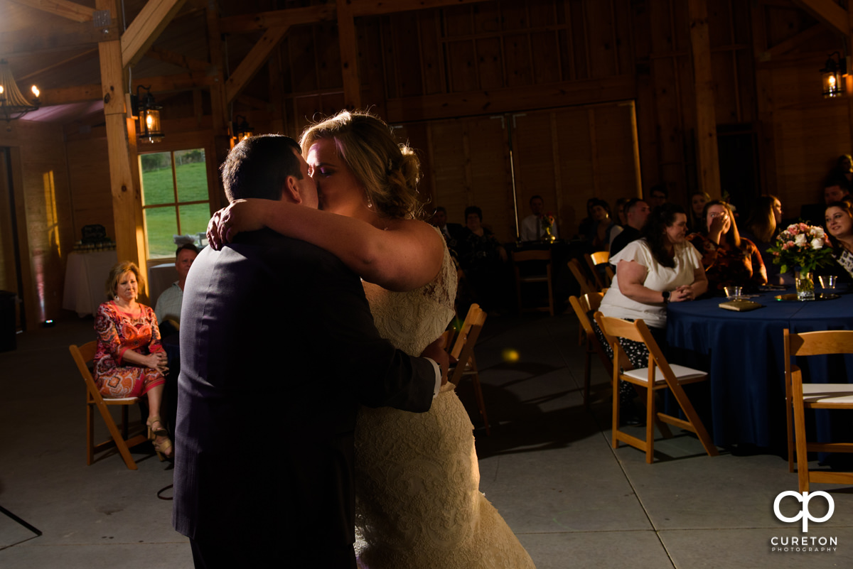 Bride and groom kissing during their first dance.