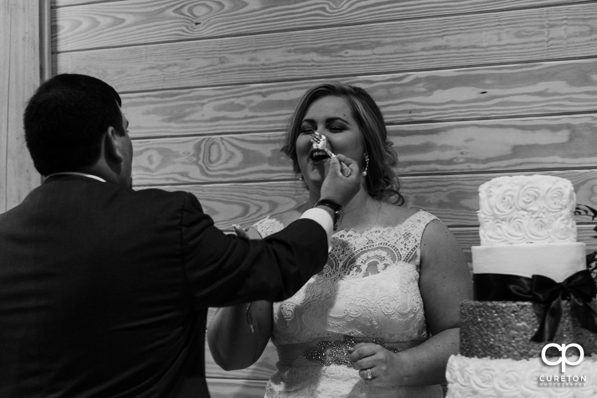 Groom feeding the bride cake.