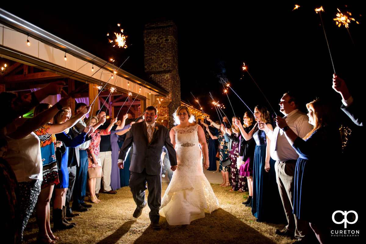 Bride and groom making a grand exit through sparklers at their South Wind Ranch wedding in Travelers Rest,SC.