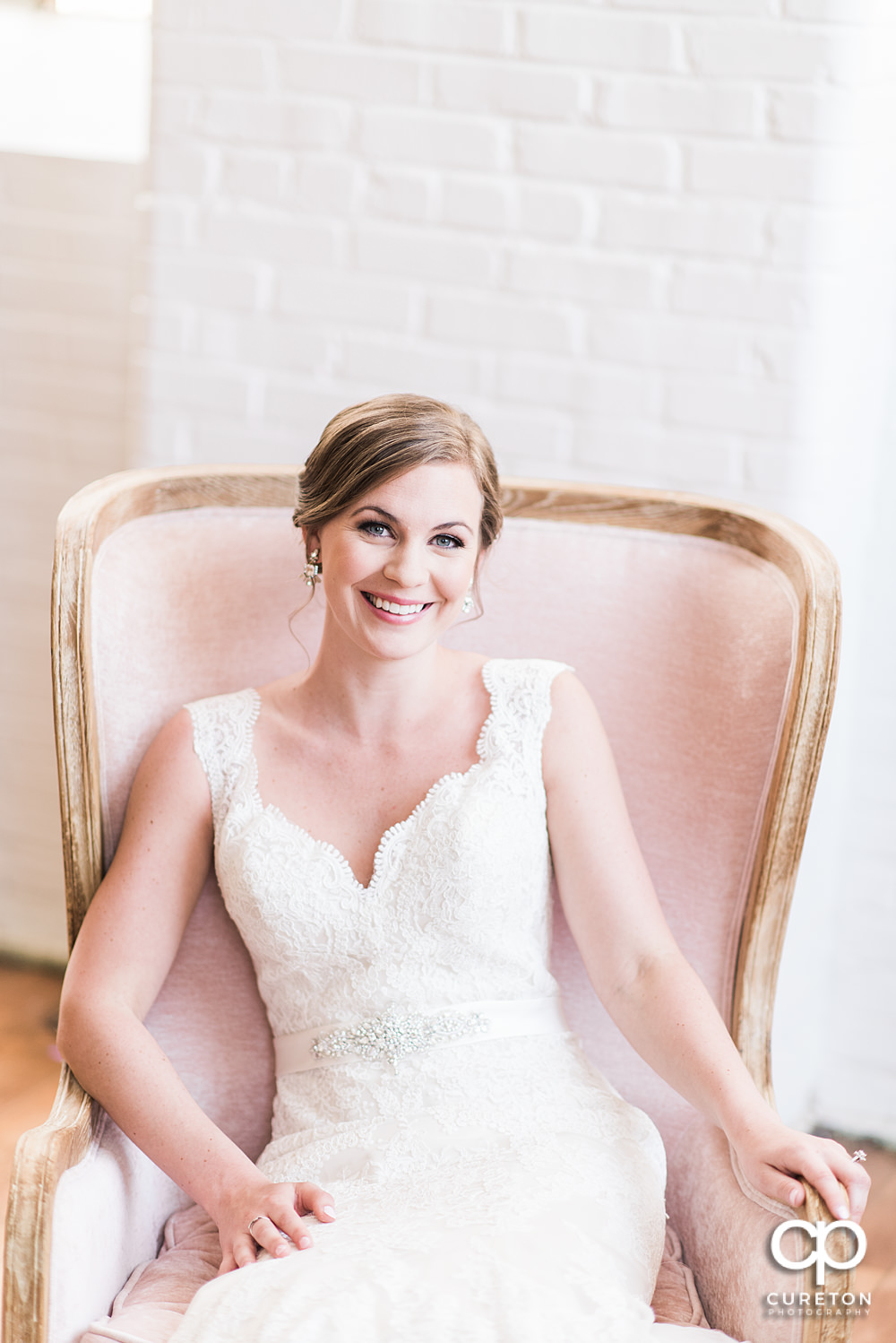 Bride sitting in a pink chair,