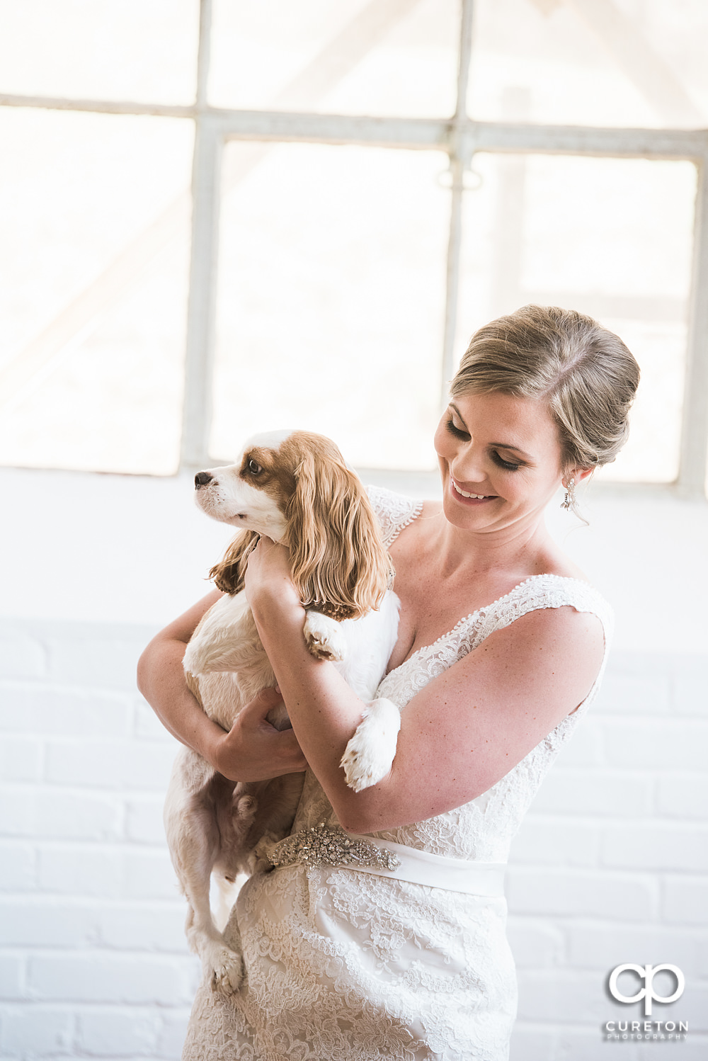 Bride and her dog laughing during her bridal session.