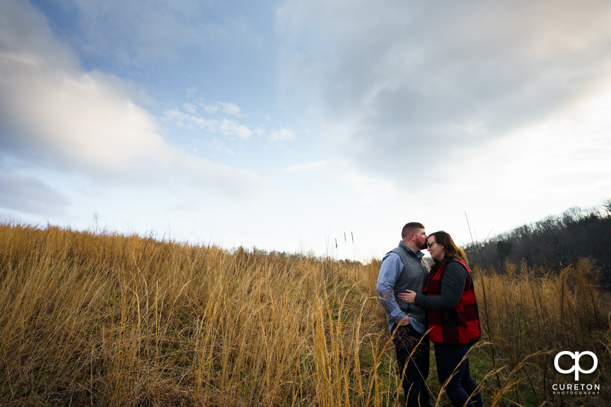 Man kissing his fiancee on the forehead durin their engagement session at South Wind Ranch.