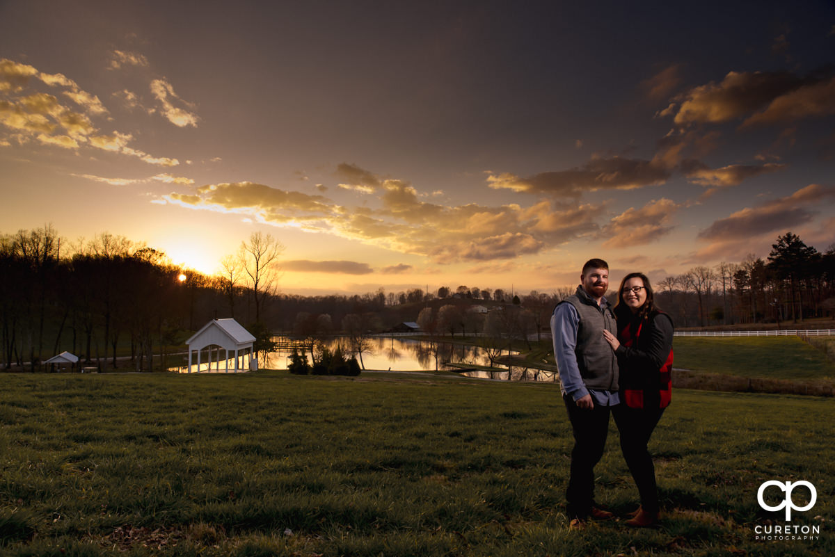 Future bride and groom at sunset in front of the chapel during a pre wedding South Wind Ranch engagement session in Travelers Rest,SC.