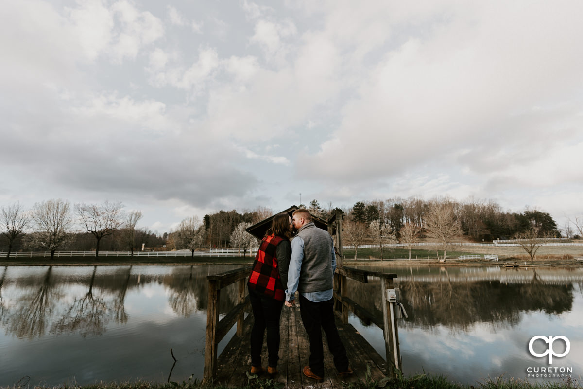 Engaged couple kissing on the dock in front of the pond during a pre wedding South Wind Ranch engagement session in Travelers Rest,SC.