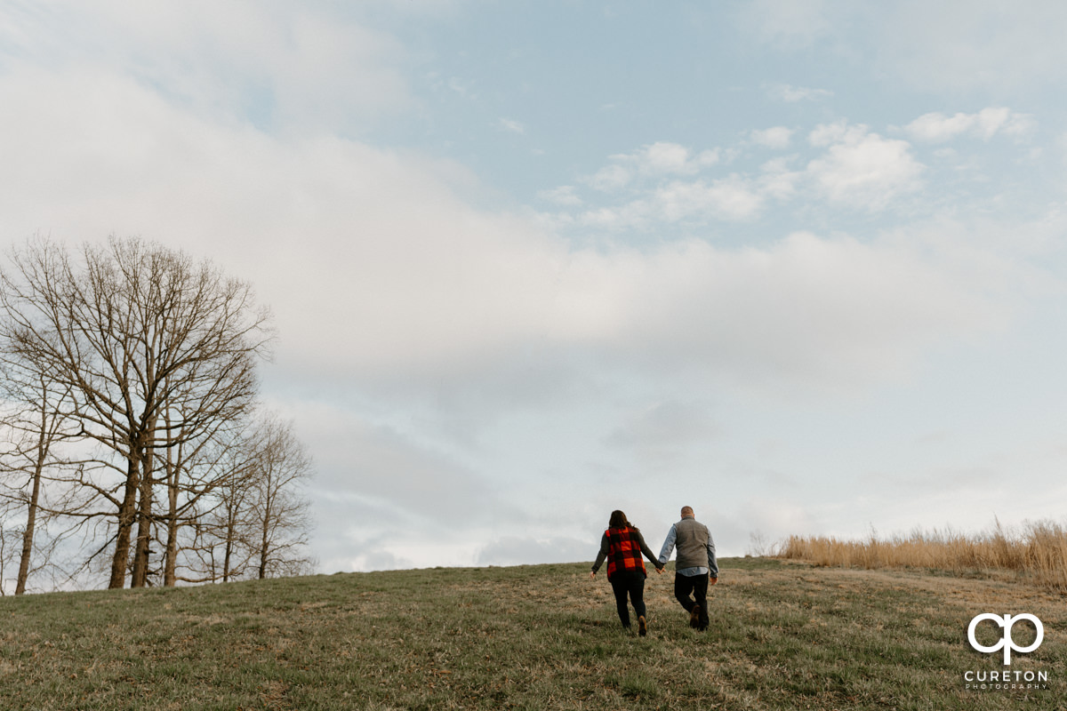 Engaged couple walking in the meadow during a pre wedding South Wind Ranch engagement session in Travelers Rest,SC.