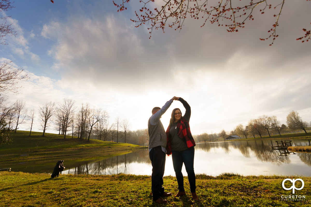 Engaged couple dancing in front of a lake.