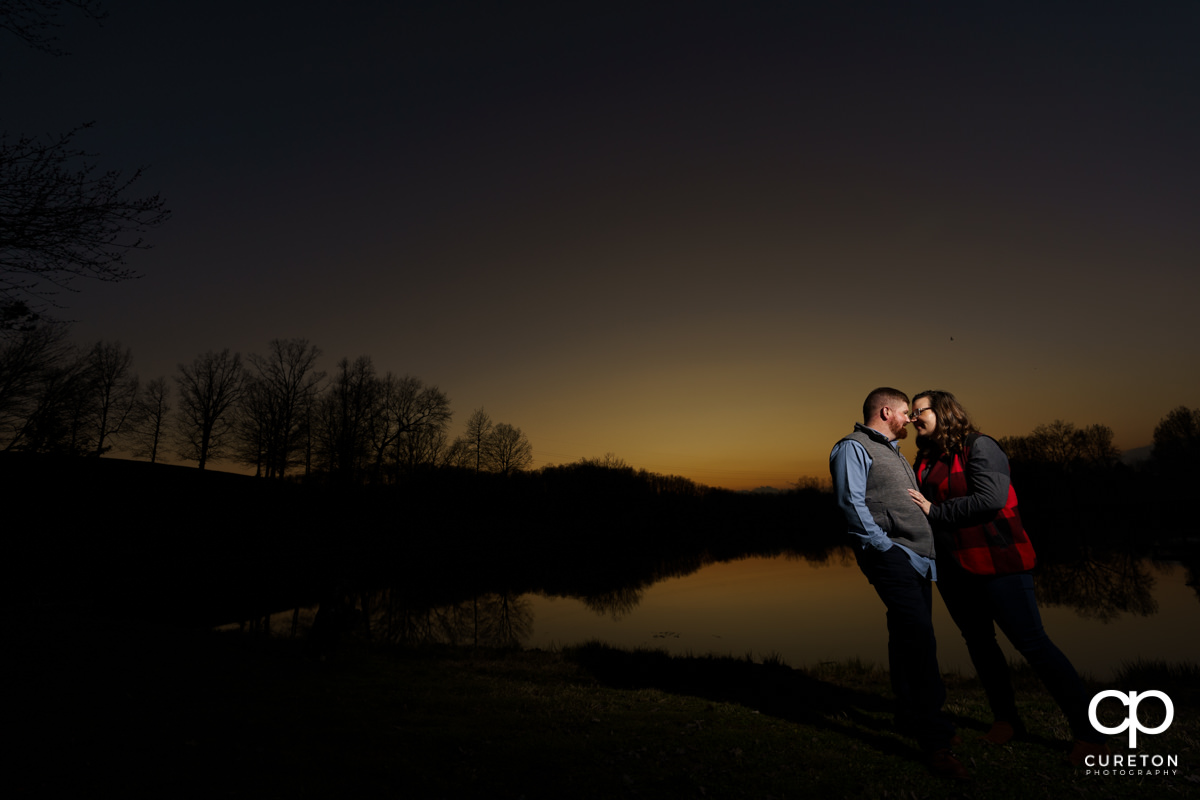 Engaged couple playing by the lake during a pre wedding South Wind Ranch engagement session in Travelers Rest,SC.