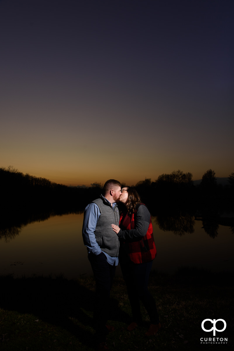 Engaged couple kissing at sunset at South Wind Ranch.