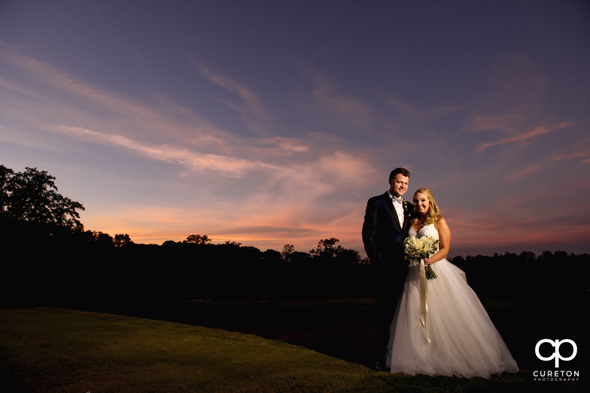 Bride and groom on the golf couse at sunset after their Spartanburg Country Club wedding.