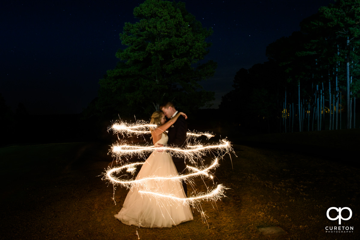 Bride and groom surrounded by sparks from a sparkler at night.